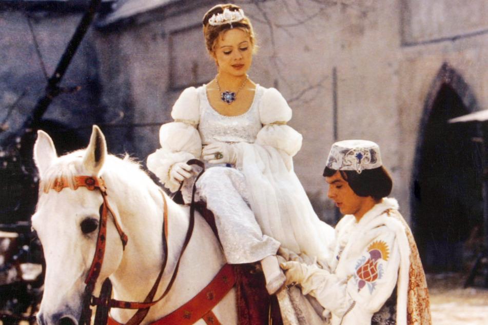 """Der Prinz (Pavel Travnicek) passt Aschenbrödel (Libuse Safrankova) im Film """"Drei Haselnüsse für Aschenbrödel"""" den verlorenen Schuh an."""