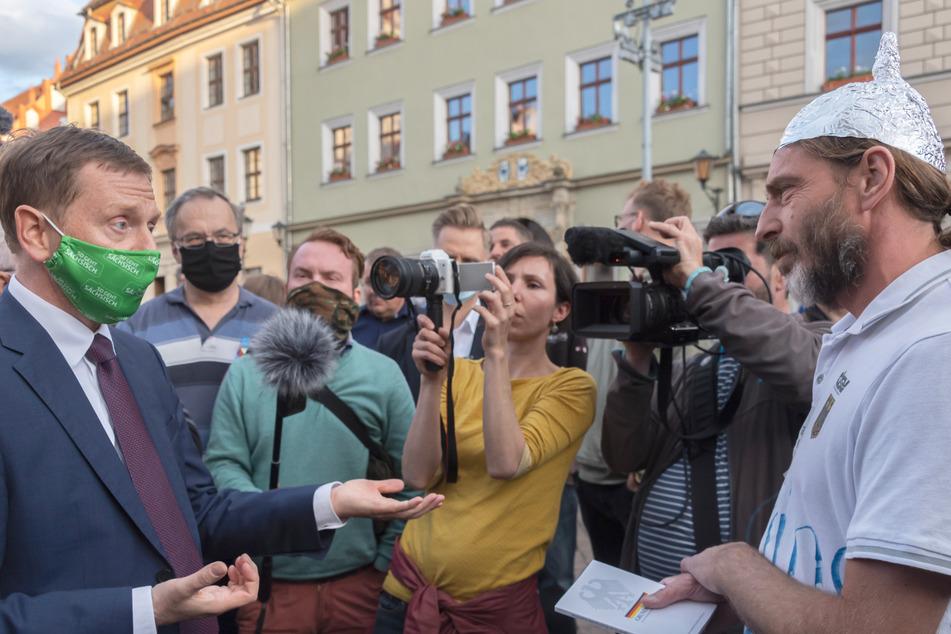 Sachsens Ministerpräsident Michael Kretschmer (45, CDU, l) spricht mit einem Gegner der Corona-Maßnahmen.