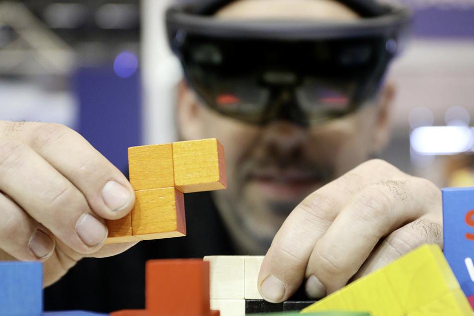 """Ein Mann stellt auf der Sonderschau """"Digitale Innovationen"""" verschiedener Universitäten auf der didacta mit Hilfe einer HoloLens den Zusammenbau des Lern- und Geduldsspiels """"Soma-Würfel"""" vor. (Archivbild)"""