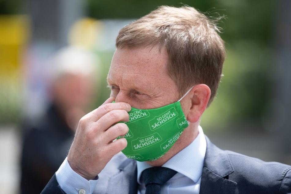 Michael Kretschmer (CDU), Ministerpräsident von Sachsen, der einen grünen Mundschutz trägt, fasst sich während der Übergabe von Schutzmasken an die Nase.
