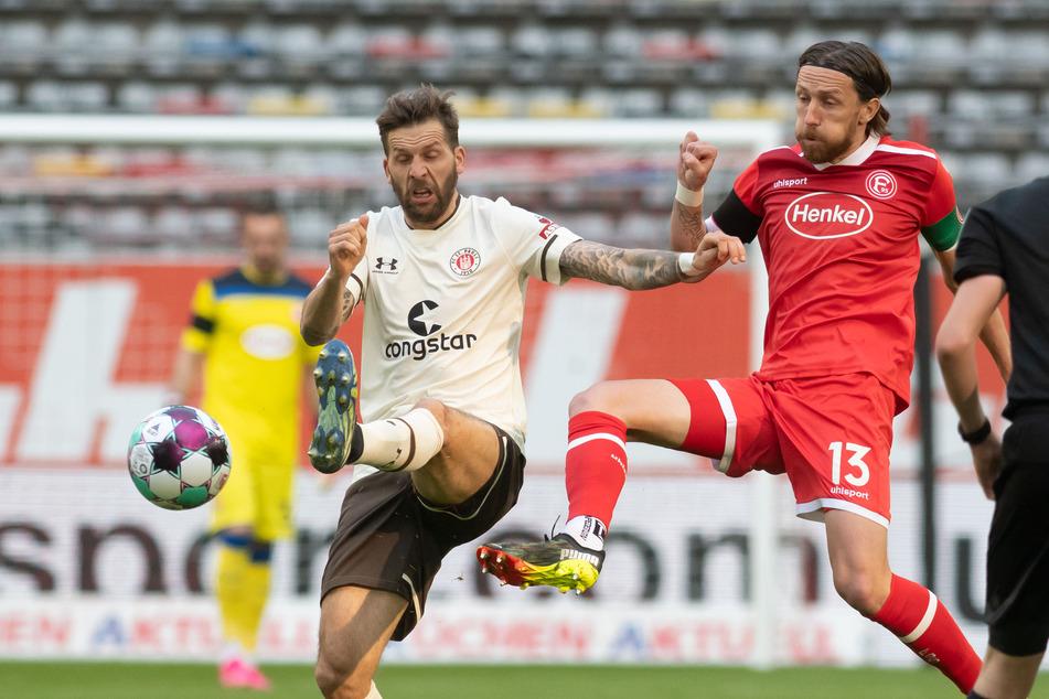 Startelf-Rückkehrer Guido Burgstaller (l.) konnte dem Spiel des FC St. Pauli nicht seinen Stempel aufdrücken, wurde von den Düsseldorfern um Adam Bodzek (r.) abgemeldet.