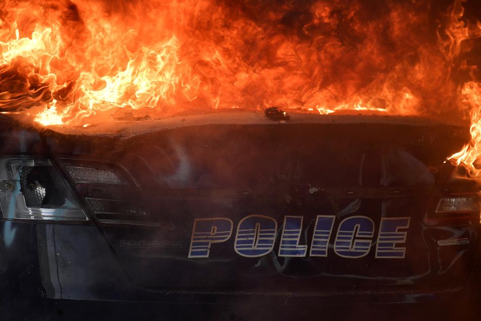 Ein Fahrzeug der Polizei von Atlanta brennt während einer Demonstration gegen Polizeigewalt. Der Protest richtet sich nach dem gewaltsamen Tod des Afroamerikaners Floyd gegen Rassismus und Polizeigewalt.