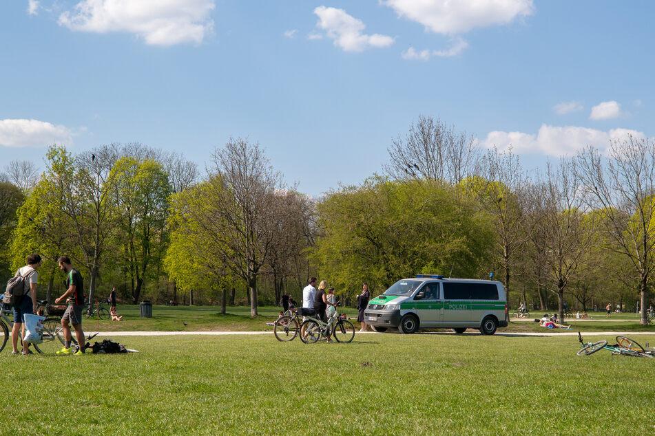 Polizisten fahren in einem Einsatzwagen durch den Englischen Garten im Herzen Münchens.