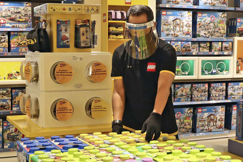 Ein Angestellter in Schutzkleidung ordnet Kisten mit Lego in einem Spielzeuggeschäft