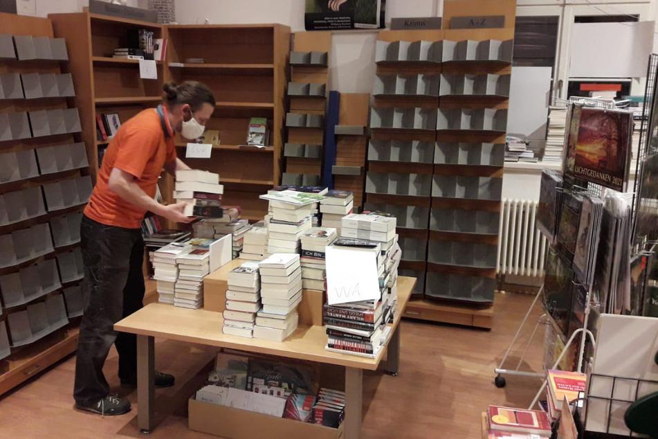 Mitarbeiter Konrad Wiehl sortiert Bücher für die Umzugskisten.