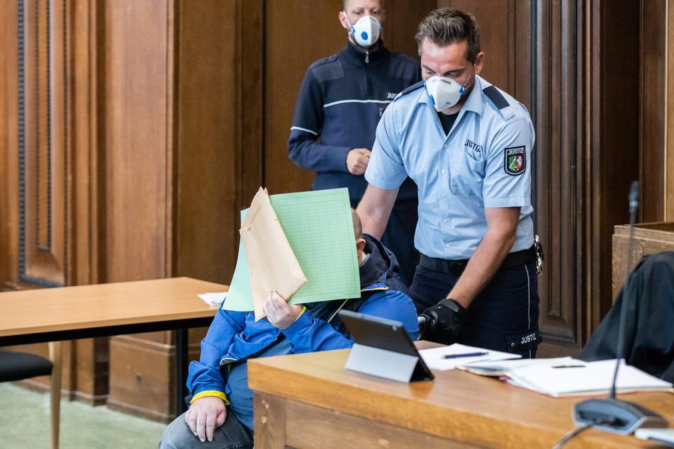 Einer der beiden Angeklagten wird im Rollstuhl und mit einer Mappe vor dem Gesicht vor Beginn der Verhandlung in den Gerichtssaal des Landgerichts geschoben.