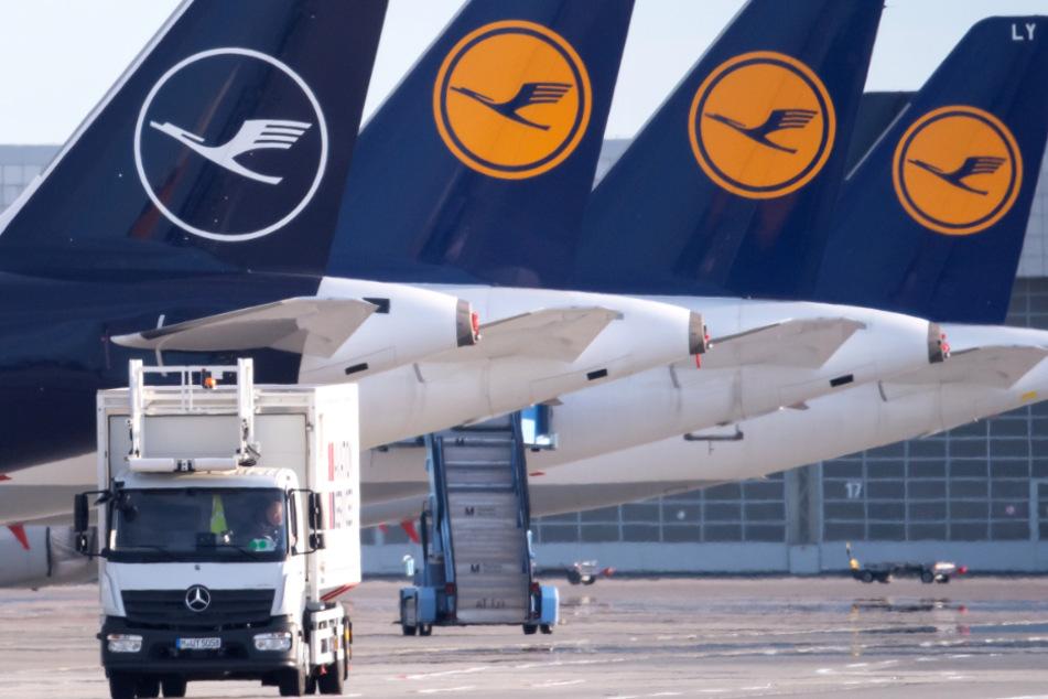 Flugzeuge der Lufthansa stehen auf dem Vorfeld eines Flughafens.