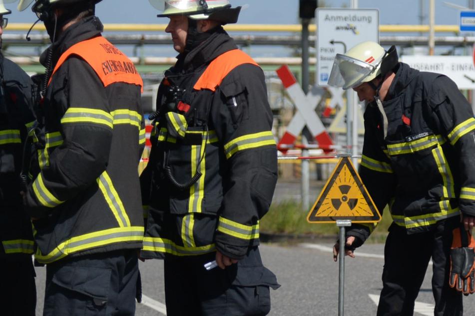 Ein Feuerwehrmann stellt ein Warnschild vor dem Betrieb auf.