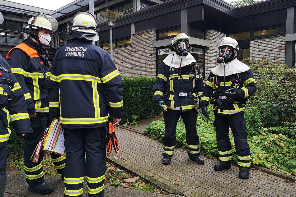 Einsatzkräfte der Feuerwehr stehen vor der Schwimmhalle in Hamburg-Bergedorf.