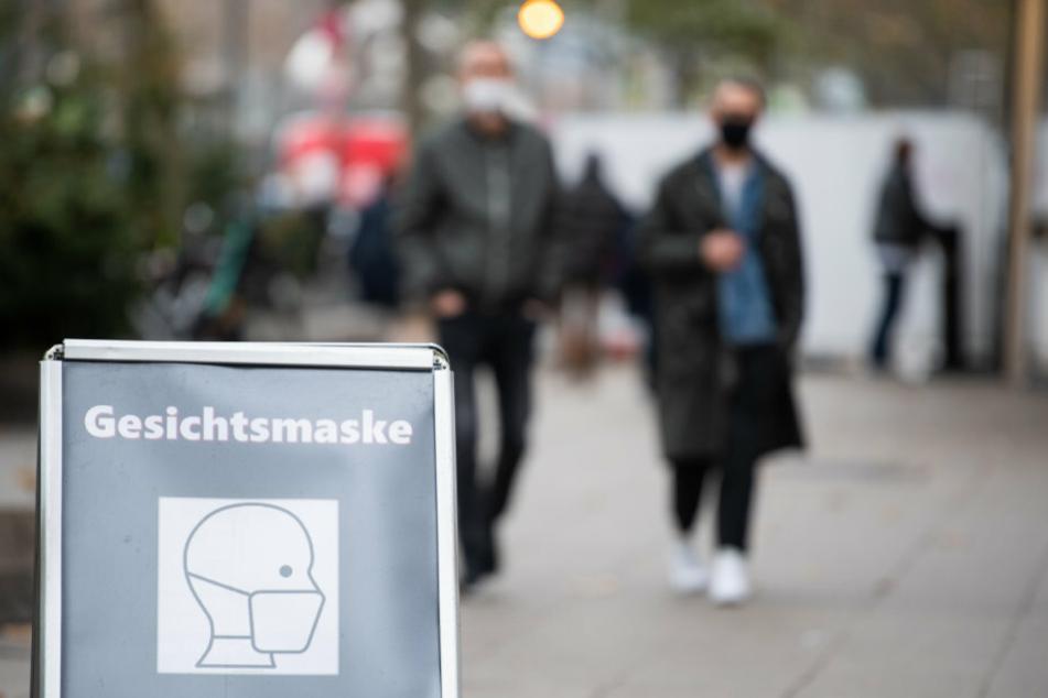 """In einer Einkaufsstraße steht ein Schild mit der Aufschrift """"Gesichtsmaske""""."""