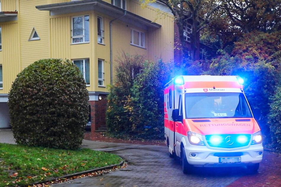Ein Rettungswagen steht mit Blaulicht vor dem Ort des Unglücks.