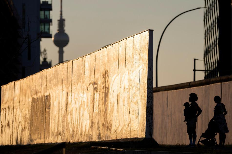 Eine Familie schaut sich an der East Side Gallery im Abendlicht ein Stück der Berliner Mauer an.