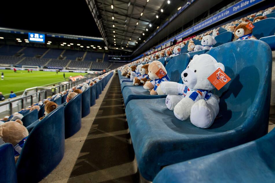 Keine Fans wegen der verschärften Coronamaßnahmen, aber auf der Tribüne sitzen 15.000 Teddybären mit einem Fußballtrikot.