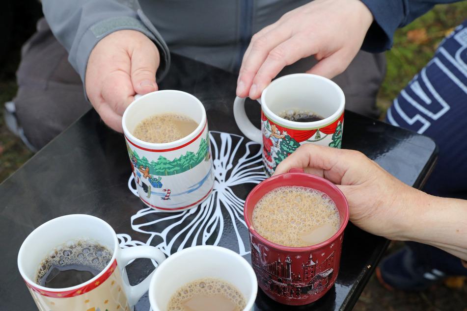 Vor dem Kältebus einer Obdachlosenhilfe greifen Bedürftige nach Kaffeetassen mit weihnachtlichen Motiven.