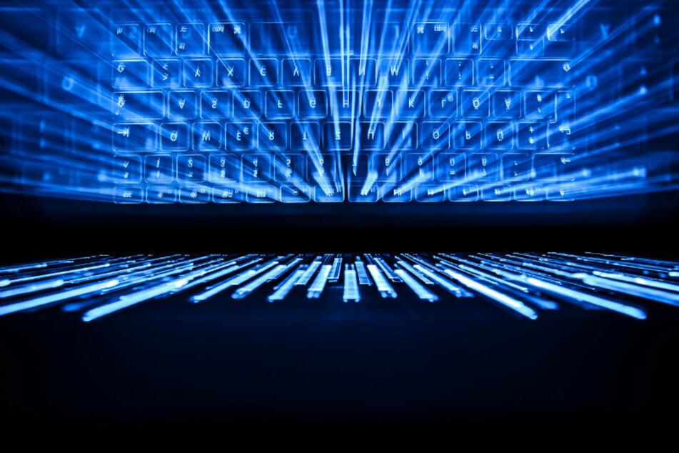 Die beleuchtete Tastatur eines Laptops spiegelt sich im Bildschirm. (Archivbild)