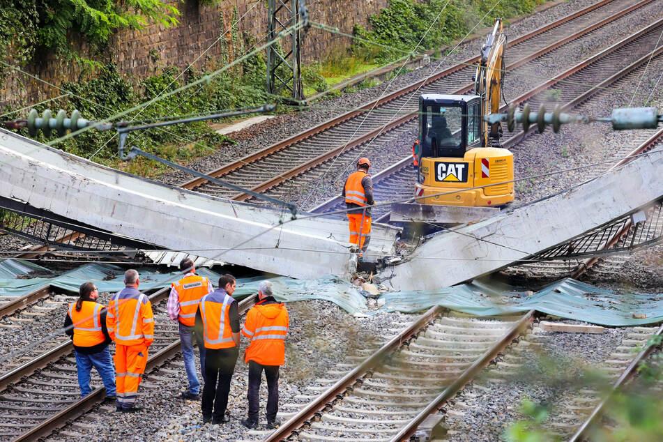 Arbeiter untersuchen Teile einer Brücke, die auf den Gleisen liegen.