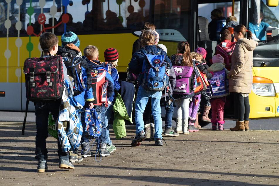 Mehrere Schüler steigen vor einer Gemeinschaftsschule in einen Schulbus ein. (Archivbild)