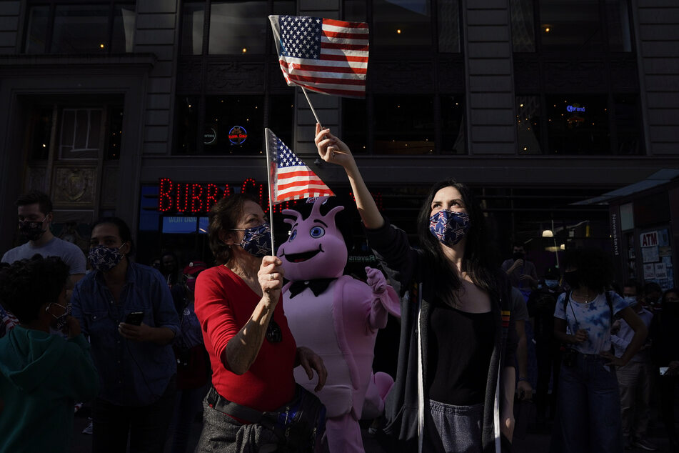 Menschen feiern mit kleinen USA-Fahnen auf dem Times Square in New York den Sieg von Joe Biden.