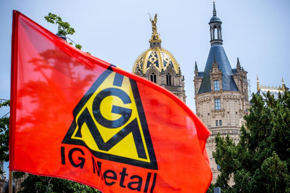 Eine Fahne der IG Metall weht bei einer Demonstration von Werftarbeitern vor dem Landtagssitz.