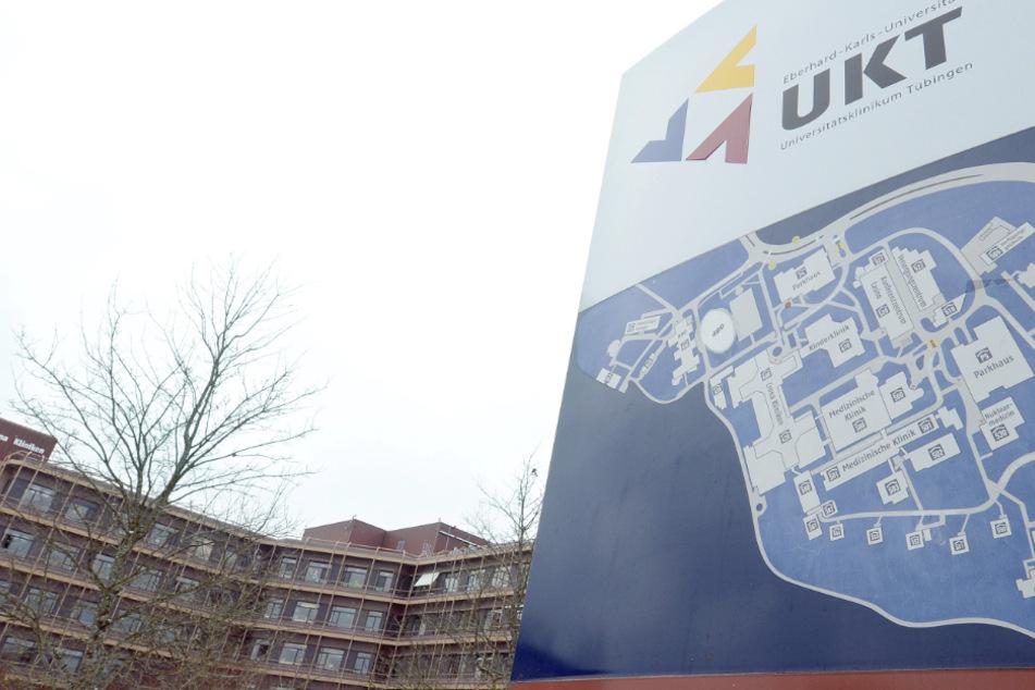 Ein Logo mit einem Hinweisschild des Universitätsklinikums Tübingen steht vor einem Klinikgebäude.