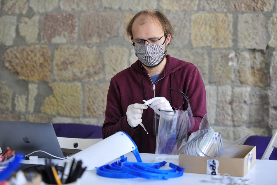 Organisator Michael Storz (33) schneidet mit einem Lasercutter die Folien für die Schutzvisiere zurecht.