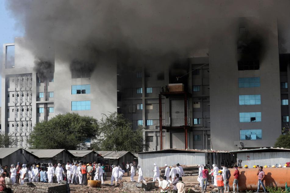 """Mitarbeiter verlassen die Gebäude des """"Serum Institute of India"""", nachdem ein großes Feier ausgebrochen ist."""