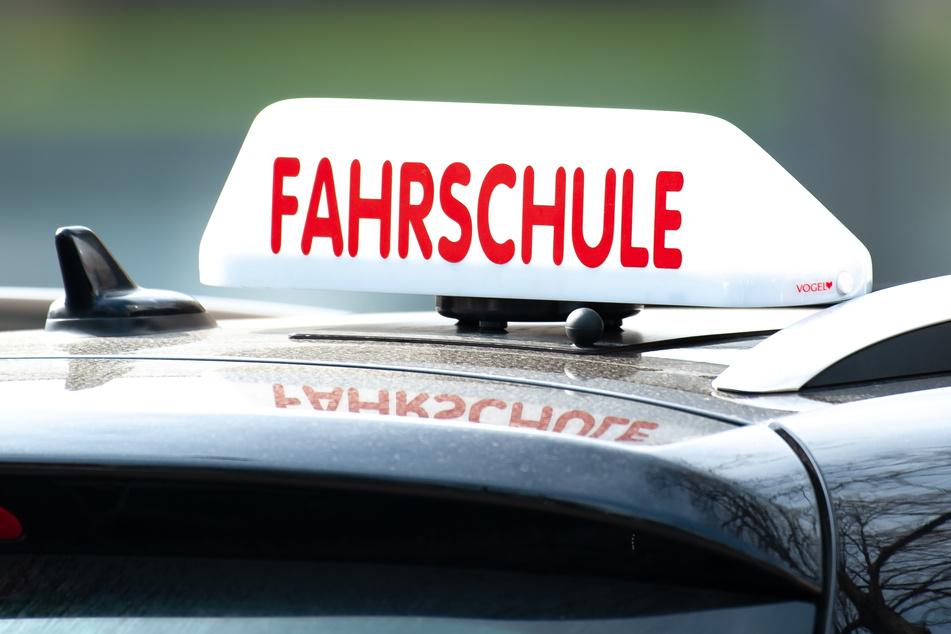 """Ein Schild mit der Aufschrift """"Fahrschule"""" ist auf einem Fahrschulauto befestigt."""