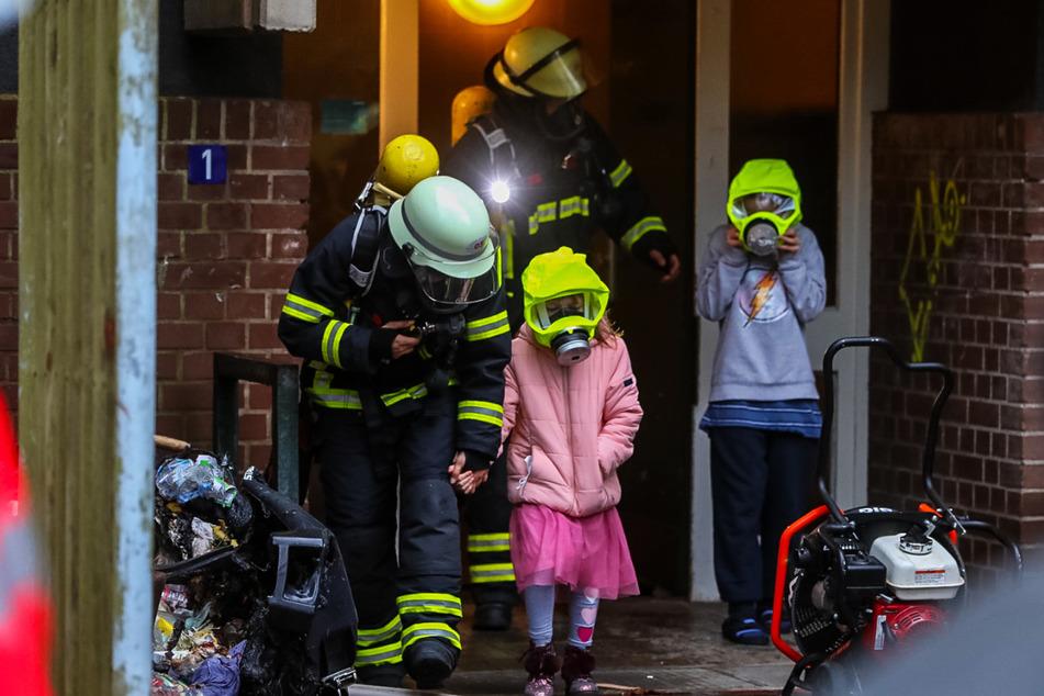 Feuerwehrleute bringen die drei Kinder aus dem Haus.