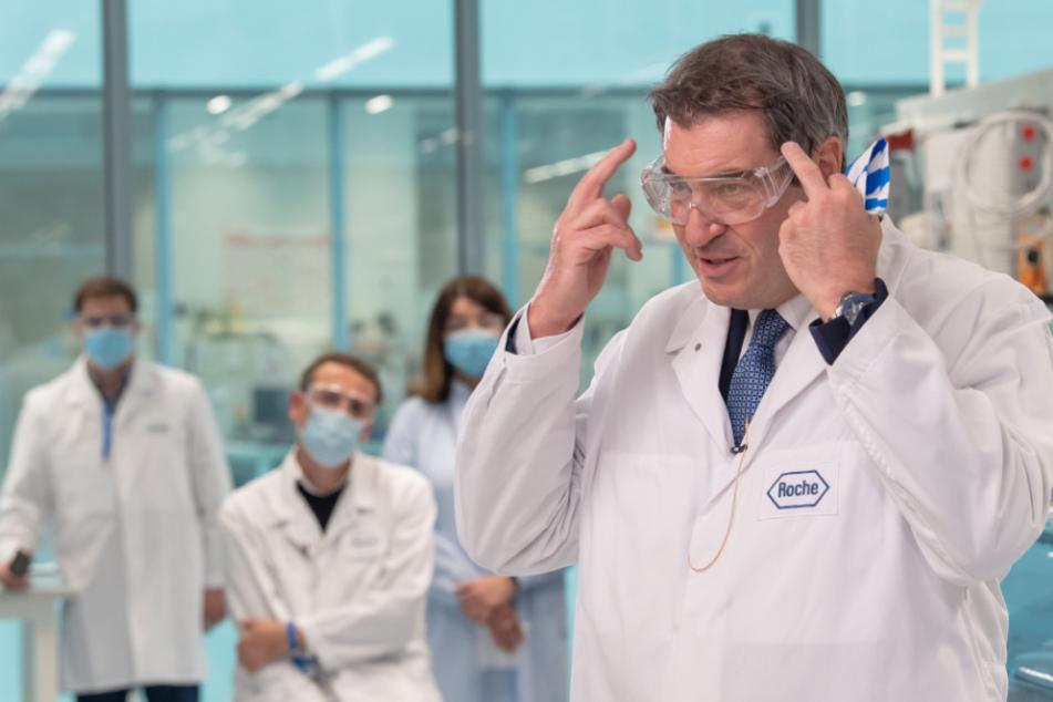 Markus Söder (CSU), Ministerpräsident von Bayern, steht mit Schutzbrille im Roche-Entwicklungslabor für den neuen serologischen Antikörpertest Elecsys Anti-SARS-CoV-2 und gestikuliert.