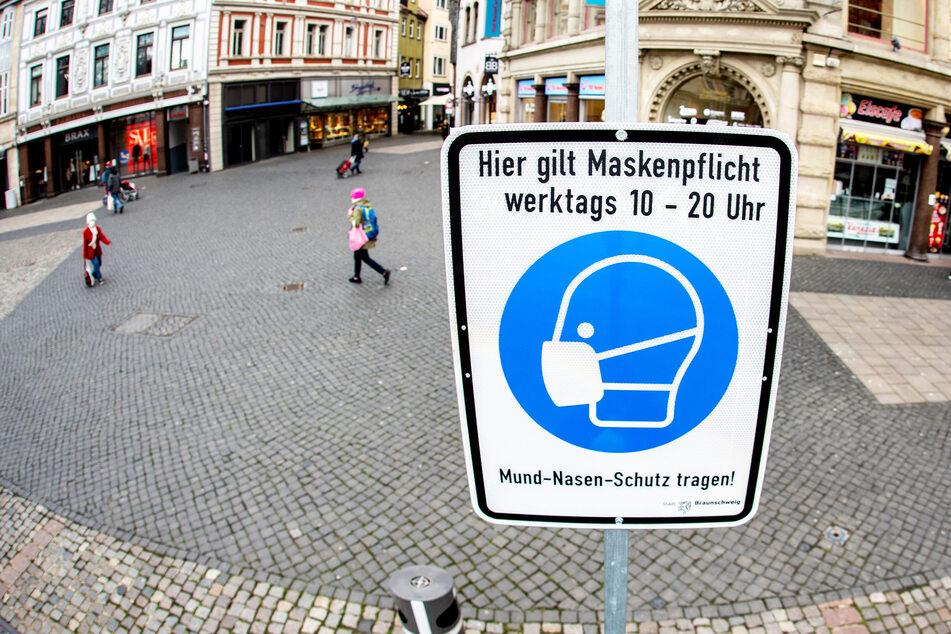"""Ein Schild mit der Aufschrift """"Hier gilt Maskenpflicht"""" steht in der nahezu menschenleeren Innenstadt Braunschweigs."""