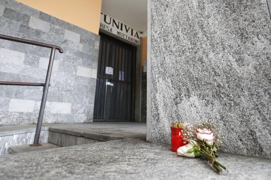 Blumen und eine Kerze liegen vor der Abfahrtsstation der Seilbahn von Stresa nach Mottarone. Beim Absturz einer Gondel einer Seilbahn am norditalienischen Lago Maggiore am 23. Mai haben 14 Menschen ihr Leben verloren.