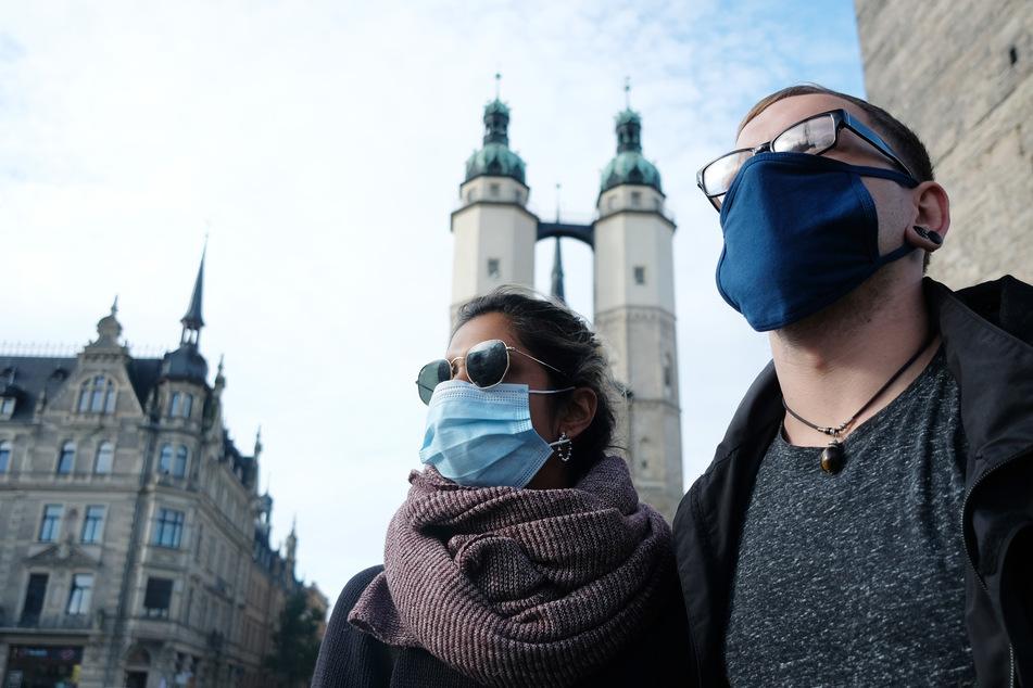 Passanten mit Mund- und Nasenschutz auf dem Marktplatz in Halle. Sachsen-Anhalts Bürger sind mehrheitlich gegen eine Steuererhöhung, um die Folgen der Corona-Pandemie zu stemmen.