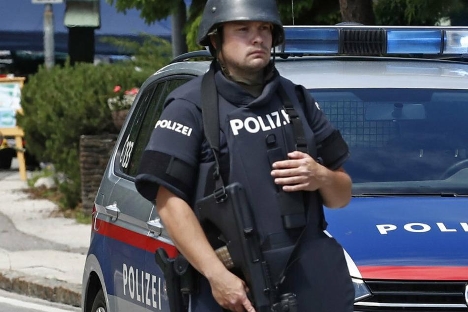 Ein Polizist aus Österreich steht vor einem Polizeiauto (Symbolbild). Dank dem Eingreifen der Beamten konnte bei der Demo schlimmeres verhindert werden.