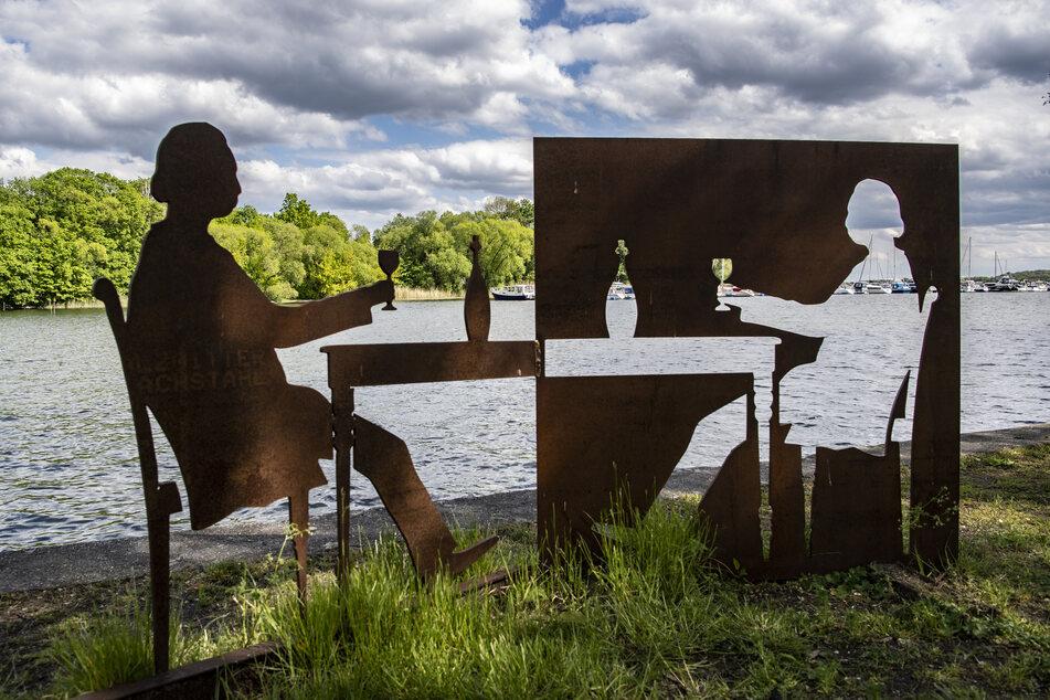 """Das Kunstwerk """"Mit Fontane zu Tisch von Jessica Dörhöfer steht am Ufer in der brandenburgischen Kommune Plaue. Für Besucher aus einem Stadt- oder Landkreis mit erhöhtem Infektionsgeschehen gilt in einigen Bundesländern ein Beherbergungsverbot."""