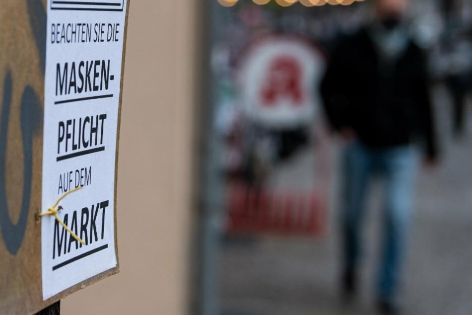"""An einem Baum hängt ein Schild mit der Aufschrift """"Achtung - Beachten Sie die Maskenpflicht auf dem Markt""""."""