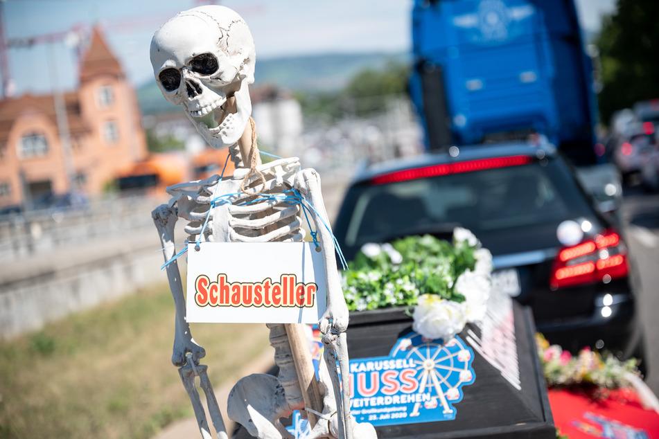 """Ein Skelett mit einem Zettel, auf dem """"Schausteller"""" steht, wird während einer Demonstration des Schaustellerverbandes Im Juli 2020 durch Stuttgart gefahren."""