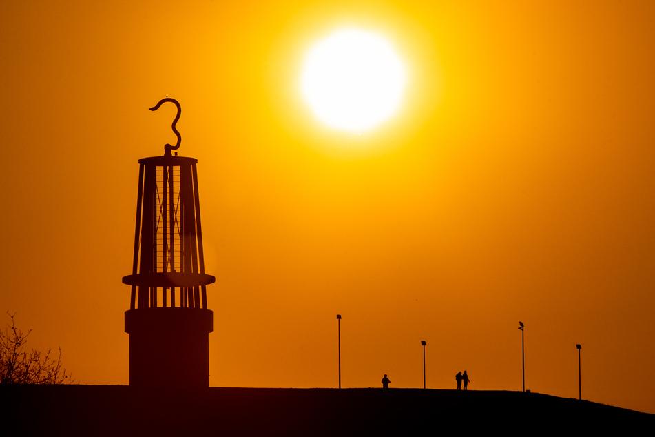 Drei Personen laufen beim Sonnenuntergang auf der Halde Rheinpreußen neben der Grubenlampe, einer Landmarke her.