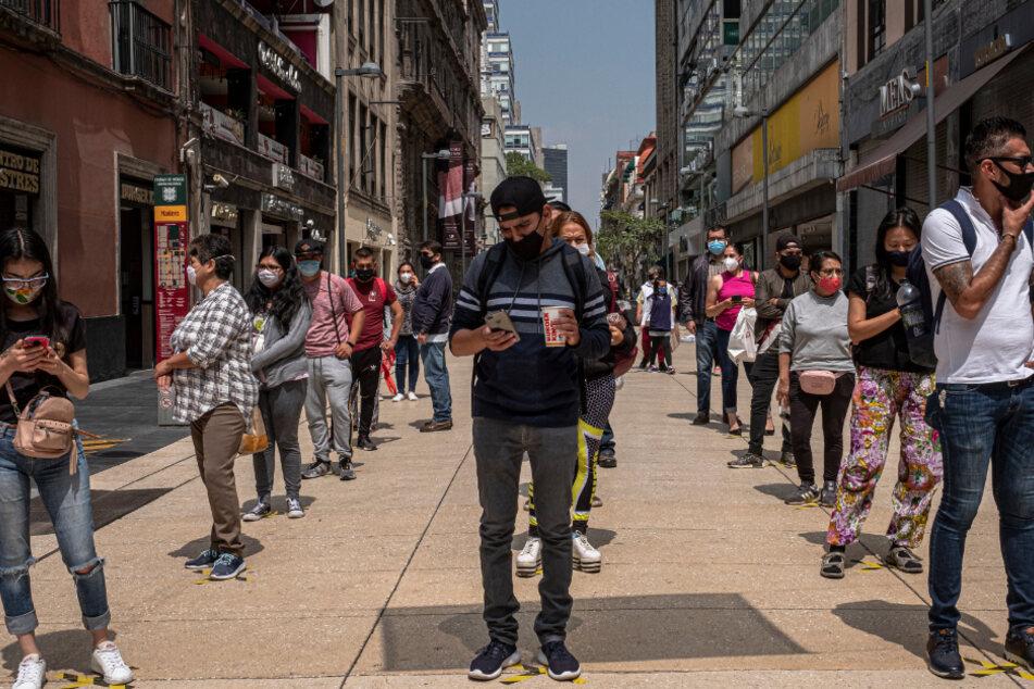 Menschen mit Mundschutzmasken stehen Schlange und halten Abstand voneinander vor dem Eingang zur Altstadt inmitten der Corona-Pandemie.