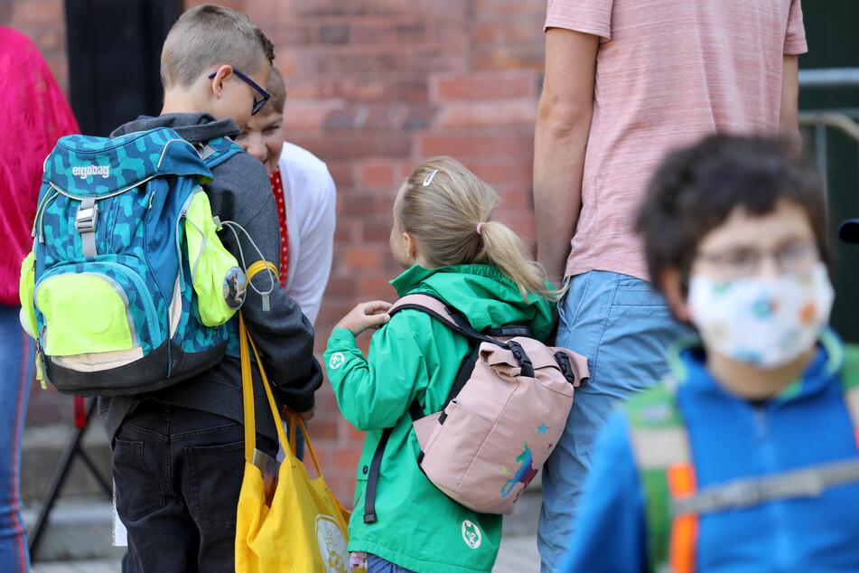 Schüler werden von ihren Eltern zur Schule gebracht.