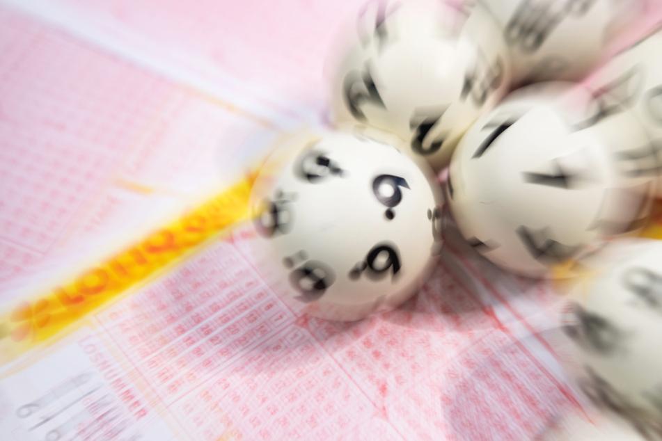 Lotto-Kugeln kullern auf einem Lottoschein... und machten einen neuen Millionär.