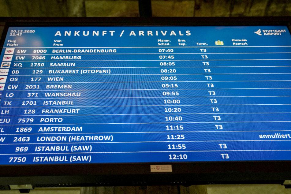 """Auf einer Anzeigetafel des Flughafens Stuttgart steht ein """"annulliert"""" Hinweis für einen Flug aus London. Wegen einer Coronavirus-Variante gibt es Landesverbote für Flüge aus Großbritannien."""
