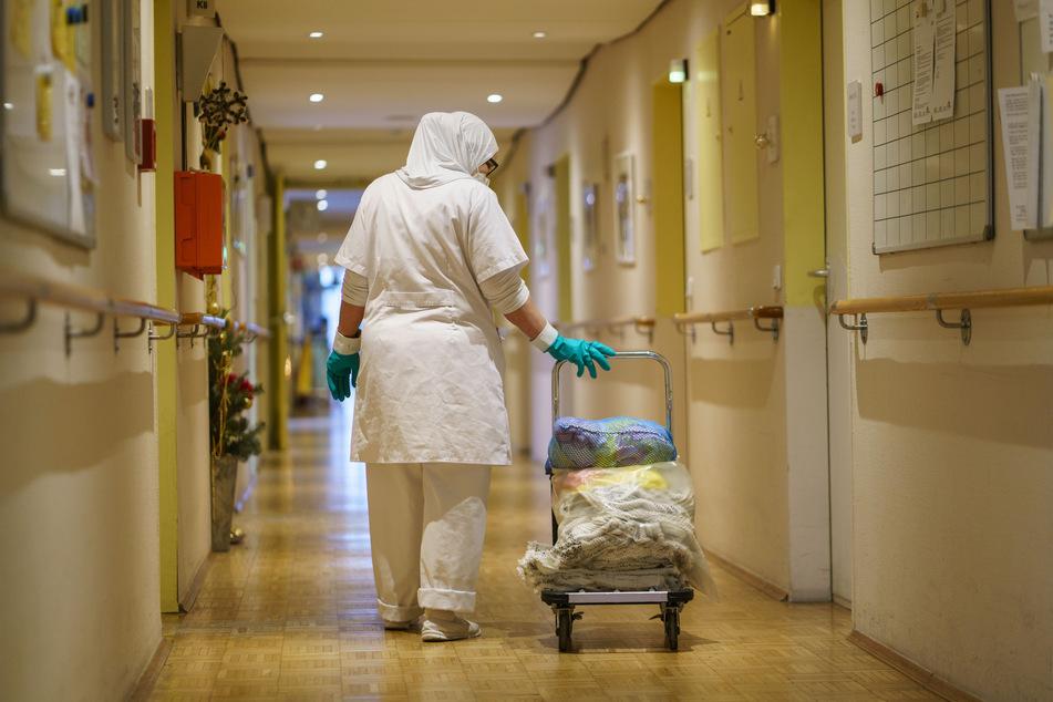 """Eine Reinigungskraft zieht einen Wagen mit Wäsche einen der Gänge eines Alten- und Pflegeheimsheims entlang. Es gebe es nun """"die Erwartung nach einer Normalisierung""""."""