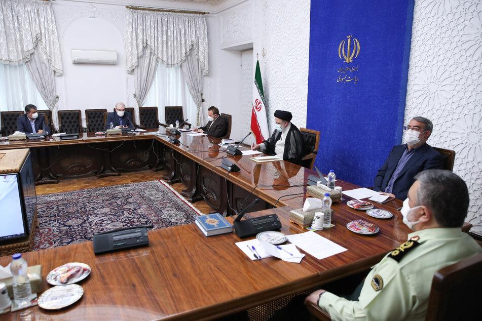 Ebrahim Raisi (3.v.r.), Präsident des Iran, nimmt an einem Treffen mit der Nationalen Task Force zur Bekämpfung der Corona-Pandemie in Teheran teil.