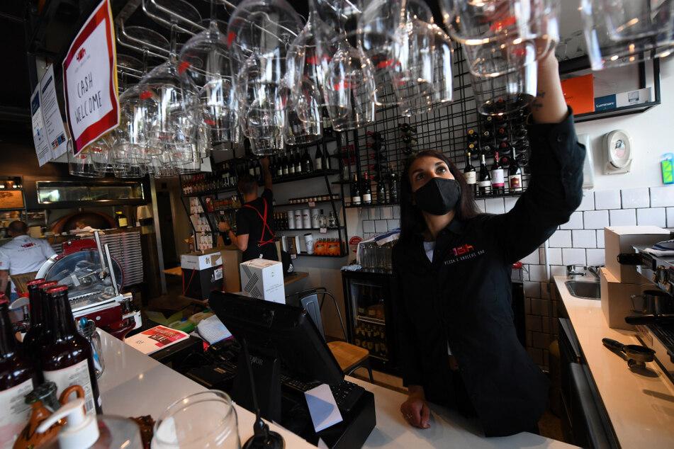 """Mitarbeiterin Nicoletta Alberici überprüft Gläser in der """"48h Pizza and Gnocchi Bar"""" vor der morgigen Wiedereröffnung."""
