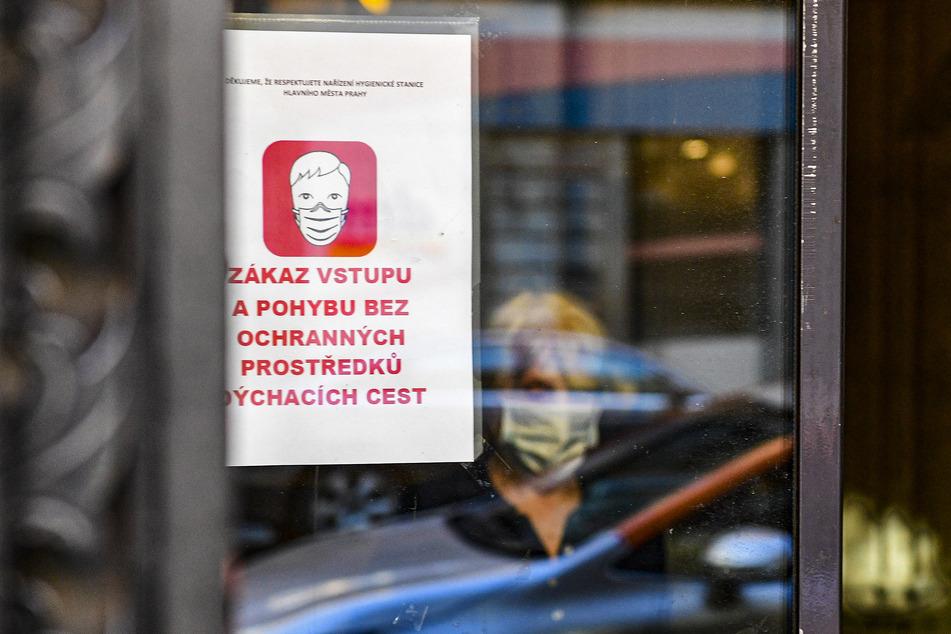 An einem Fenster einer Postfiliale hängt ein Schild, welches die Menschen darauf hinweist, einen Mundschutz zu tragen.