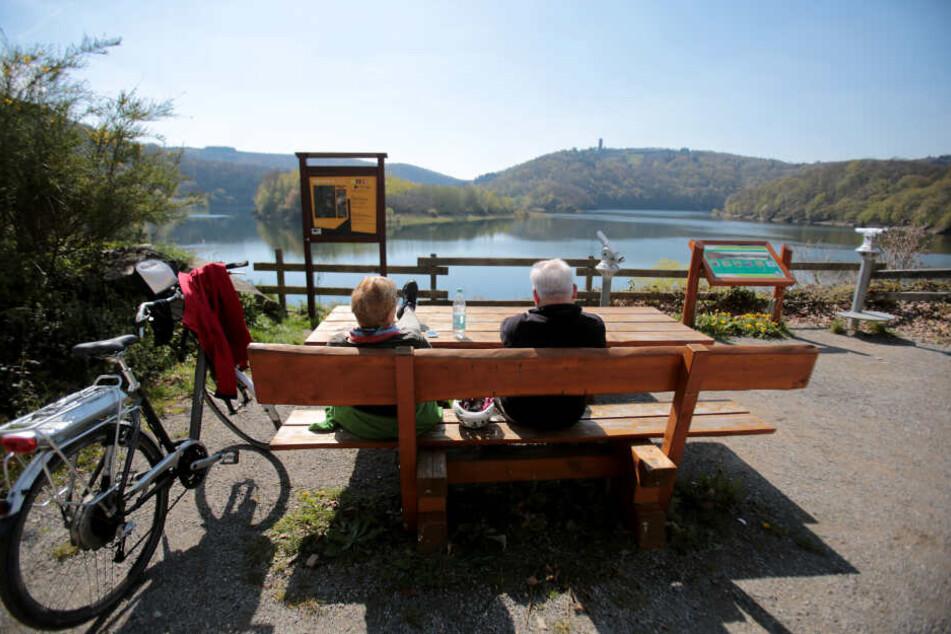 Radfahrer machen im Nationalpark Eifel am Urftsee ein Picknick.