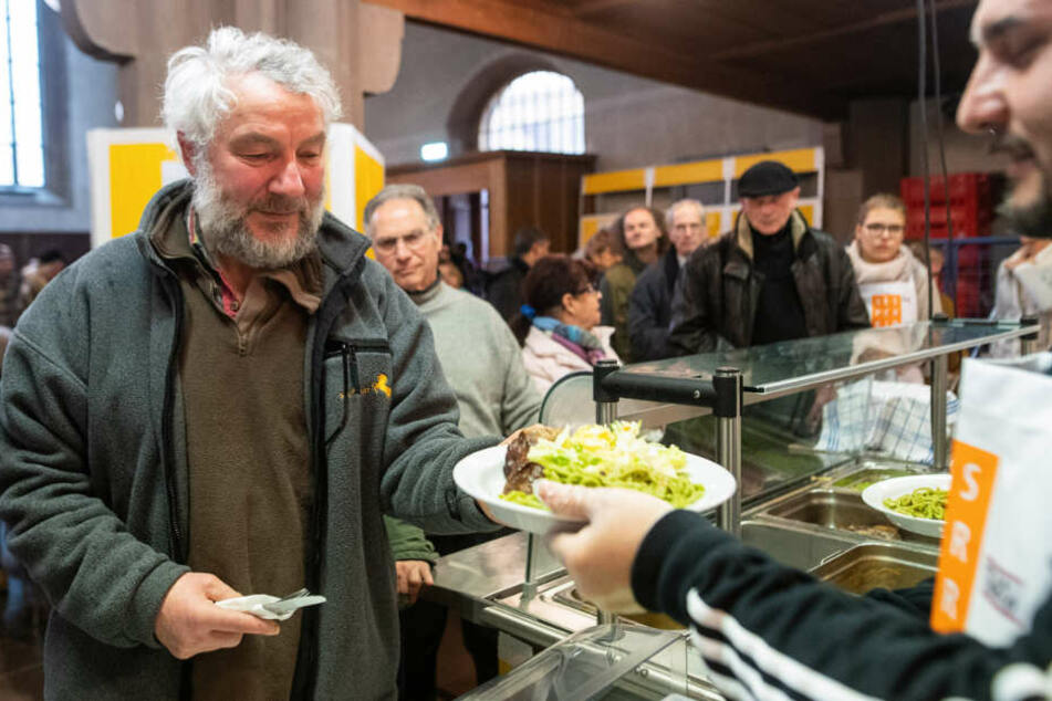 Marek nimmt sich einen Teller mit Essen in der Versperkirche.