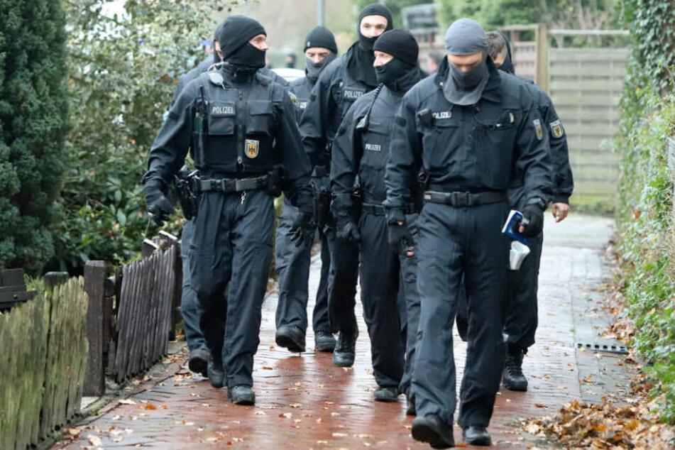 Vermummte Polizisten gehen nach dem Einsatz an einem Haus entlang.