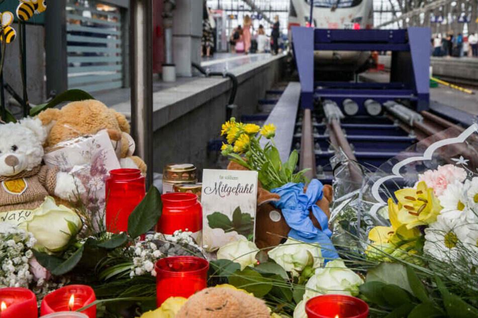 """Eine Karte mit der der Aufschrift """"In stillem Mitgefühl"""" steht am Bahnsteig 7 im Frankfurter Hauptbahnhof zwischen Kerzen, Plüschtieren und abgelegten Blumen."""