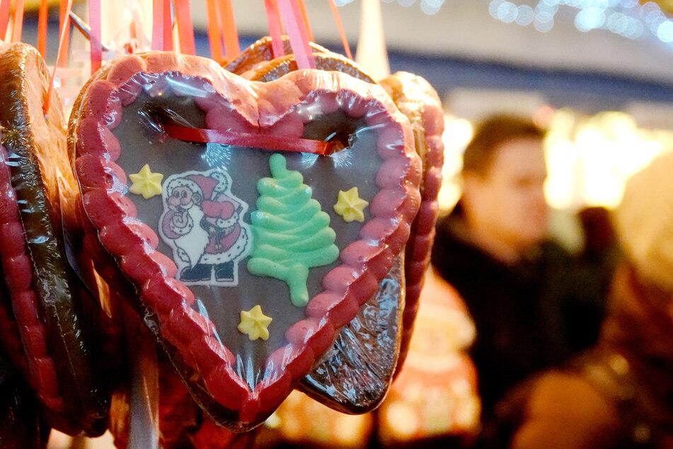 Ein Lebkuchenherz hängt an einem Stand auf einem Weihnachtsmarkt.